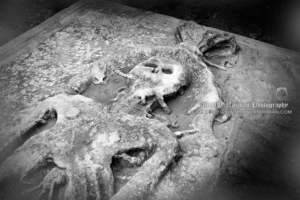 A depiction of a corpse in a shroud being eaten by worms on a grave