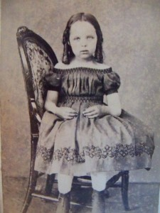 Deceased girl sat to the side on a chair so that a stand can support her body.